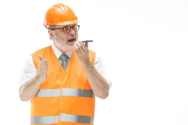 Baumeister in einer bauweste und einem orangefarbenen helm, der auf einem mobiltelefon über etwas spricht.