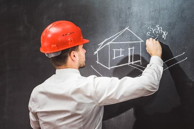 Baumeister malt haus auf tafel