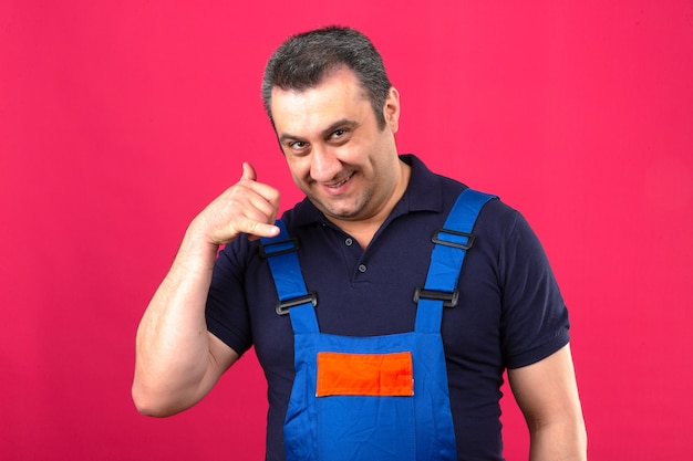 Baumeister mann, der bauuniform lächelnd macht, ruft mich zeichen mit hand und fingern über isolierte rosa wand