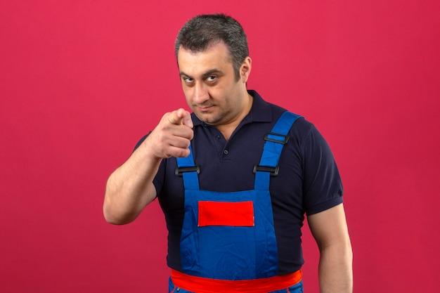 Baumeister-mann, der bauuniform trägt, die seine zeigefinger auf kamera zeigt, die sie verdächtigen ausdruck über isolierte rosa wand gestikulieren