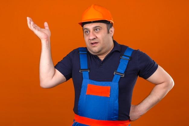 Baumeister mann, der bauuniform und schutzhelm trägt, der mit erhobener hand steht, ohne zu verstehen, was ahnungslos und verwirrter ausdruck über isolierter orange wand geschah