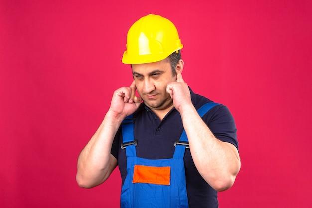 Baumeister mann, der bauuniform und schutzhelm trägt, der ohren mit den fingern mit genervtem ausdruck für den lärm über isolierter rosa wand bedeckt