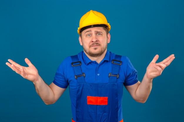 Baumeister mann, der bauuniform und sicherheitshelm ahnungslos und verwirrten ausdruck mit armen und händen trägt, erhob zweifel konzept, das über isolierter blauer wand steht