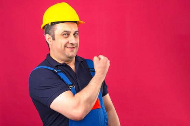 Baumeister mann, der bauuniform und sicherheitshelm trägt, der bizeps lächelnd mit glücklichem gesicht gewinnerkonzept steht über isolierter rosa wand zeigt
