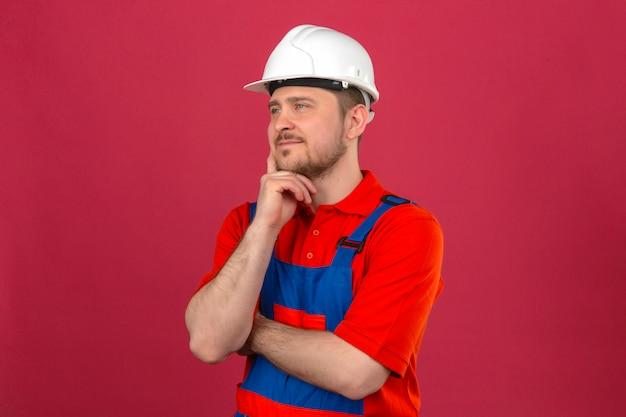 Baumeister mann, der bauuniform und sicherheitshelm trägt, der seine wange berührt und nachdenklichen blick über isolierte rosa wand steht