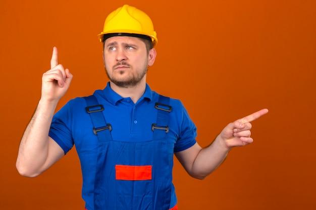 Baumeister mann, der bauuniform und sicherheitshelm trägt, warnt vor gefahr, die seinen finger anhebt, der warnzeichen mit finger zeigt, der über isolierter orange wand steht