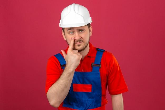 Baumeister mann, der bauuniform und sicherheitshelm trägt, zeigt auf das auge, das sie beobachtet, der verdächtigen ausdruck steht, der über isolierter rosa wand steht