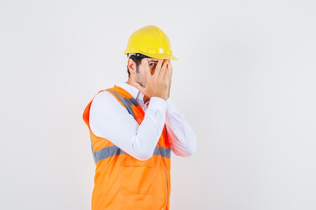 Baumeister mann, der durch finger mit einem auge im hemd, uniform schaut und verlegen aussieht.