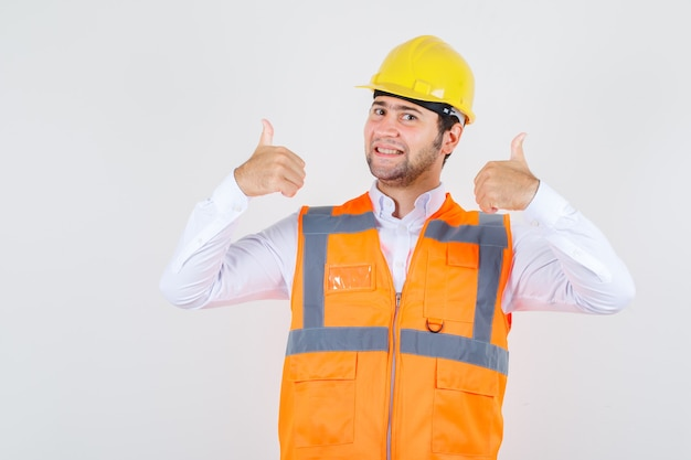 Baumeister mann im hemd, uniform zeigt daumen hoch und schaut glücklich, vorderansicht.