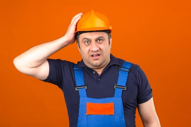 Baumeister mann trägt bauuniform und schutzhelm verwirrt und enttäuscht, keine ahnung, seinen helm über isolierte orange wand zu berühren