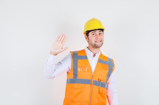 Baumeister mann winkt hand, um hallo oder auf wiedersehen in hemd, uniform und lustig aussehen zu sagen. vorderansicht.