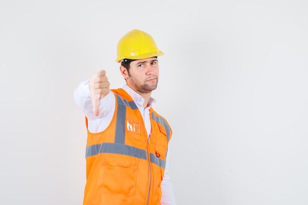 Baumeister mann zeigt daumen nach unten in hemd, uniform und sieht unzufrieden aus. vorderansicht.
