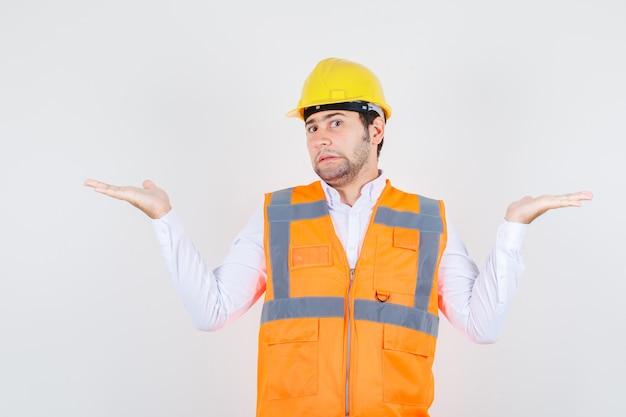Baumeister mann zeigt hilflose geste in hemd, uniform und verwirrt, vorderansicht.