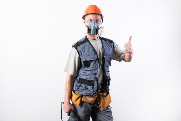 Baumeister mit einem bohrer, in einem helm und einem atemschutzgerät. daumen hoch zeigen für jeden zweck.
