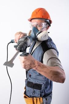 Baumeister mit einem bohrer, in einem helm und einem atemschutzgerät. für jeden zweck.