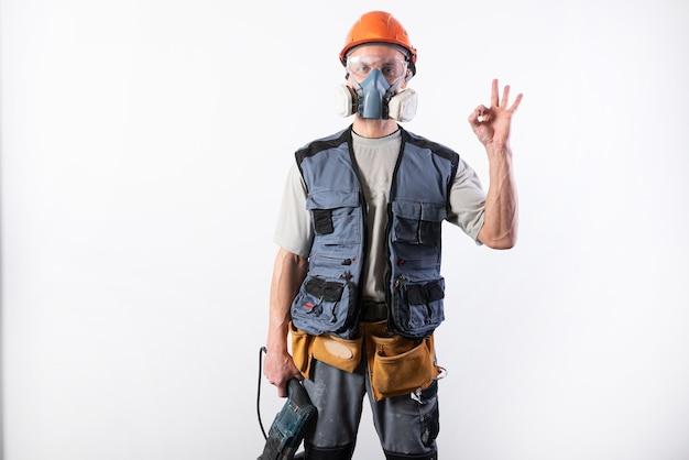Baumeister mit einem bohrer, in einem helm und einem atemschutzgerät. zeigt ein ok-zeichen für jeden zweck.