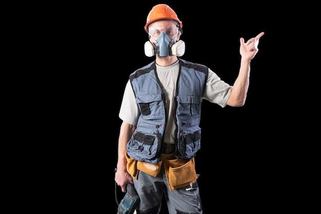 Baumeister mit einem bohrer, in einem helm und einem atemschutzgerät. zeigt nach rechts. für jeden zweck.