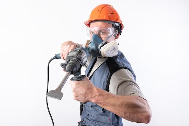 Baumeister mit einem bohrer, in einem helm und einem atemschutzgerät. zielen. für jeden zweck.