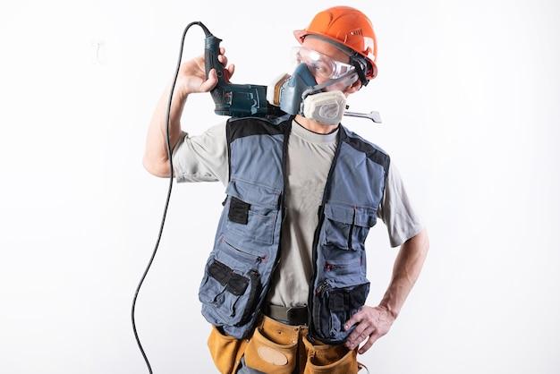 Baumeister mit einer bohrmaschine, einem helm und einer atemschutzmaske es steht mit dem gerät auf der schulter
