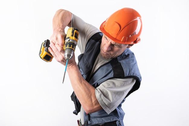 Baumeister mit lustigem gesichtsausdruck, im helm, mit akku-bohrschrauber. für jeden zweck.