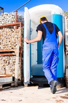 Baumeister mit mobiler toilette vor ort