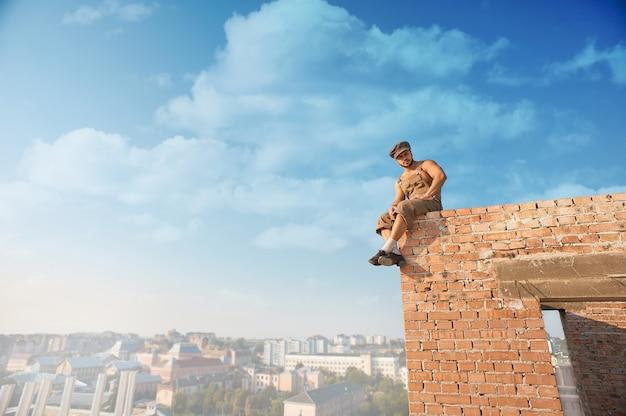 Baumeister mit nacktem oberkörper, der auf ziegelmauer sitzt