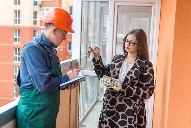 Baumeister mit notizblock und frau mit dollarbündel und schlüsseln