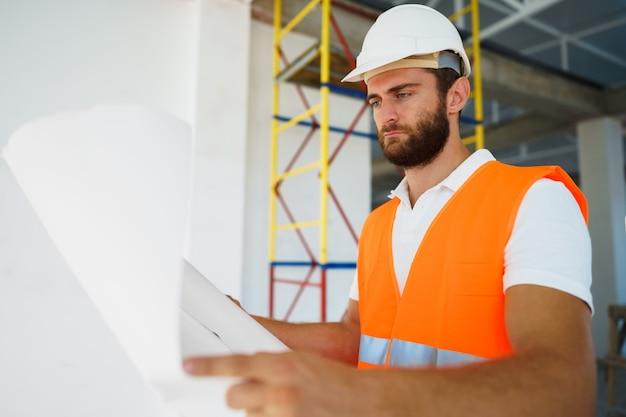 Baumeister oder architekt in bauarbeiterhelm, der ein projekt beaufsichtigt, das blaupausen betrachtet