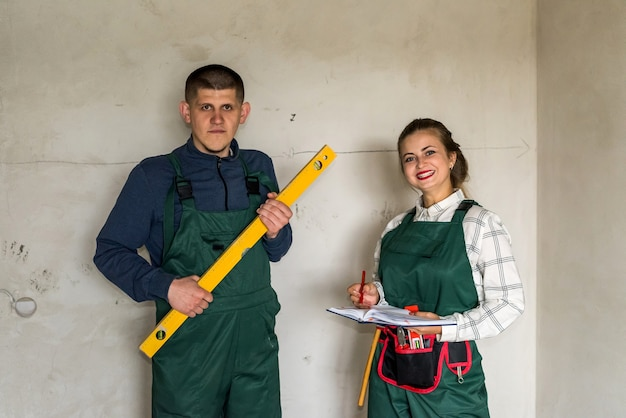 Baumeister posiert mit wasserstandsinstrument und frau mit notizblock