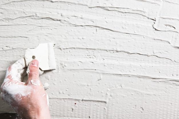 Baumeister schmutzige hand mit spachtel verteilt weißen stuck an der wand. verputzarbeiten, hausreparaturhintergrund mit freiem platz für text.
