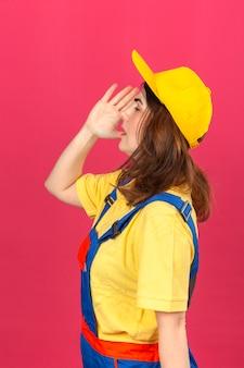 Baumeisterfrau, die bauuniform und gelbe kappe trägt, die jemanden schreien oder rufen, um mit hand nahe mund über isolierter rosa wand zur seite zu stehen