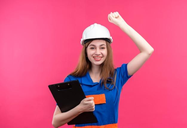 Baumeisterin der jungen frau in der bauuniform und im sicherheitshelm, die klemmbrett glücklich und fröhlich anhebende faust halten und sich über ihren erfolg freuen, lächelnd stehend über rosa wand