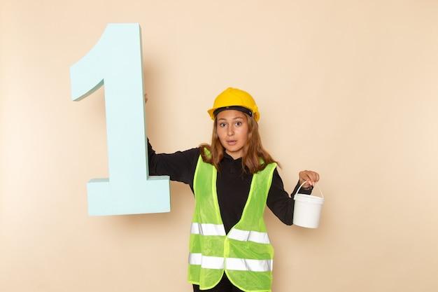 Baumeisterin der vorderansicht im gelben helm, der farbe und nummer eins figur auf dem weißen schreibtisch hält