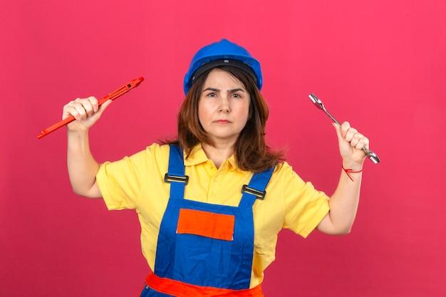 Baumeisterin, die bauuniform und sicherheitshelm trägt, die verstellbare schraubenschlüssel in erhobenen händen mit wütendem ausdruck über isolierter rosa wand halten