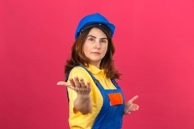 Baumeisterin, die bauuniform und sicherheitshelm trägt, präsentiert und lädt ein, mit händen zu kommen, die zuversichtlich über isolierte rosa wand schauen