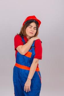 Baumeisterin, die bauuniform und sicherheitshelm trägt und unwohl ist, die schulter zu berühren, die unter schmerzen leidet, die über isolierter weißer wand stehen