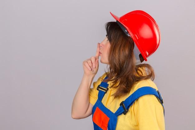 Baumeisterin in der bauuniform und im sicherheitshelm, die seitlich stehen und bitten, mit finger auf lippen stille und geheimes konzept über isolierter weißer wand ruhig zu sein