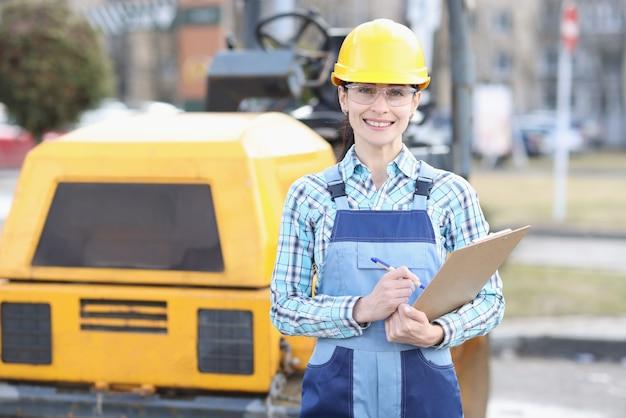 Baumeisterin in schutzhelm, die zwischenablage mit dokumenten in den händen auf dem hintergrund des asphaltfertigers hält