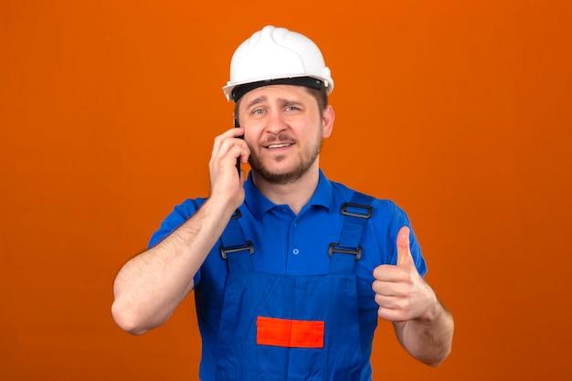 Baumeistermann, der bauuniform und sicherheitshelm trägt, der auf dem lächelnden handy des handys spricht, zeigt daumen bis zur kamera, die über isolierter orange wand steht