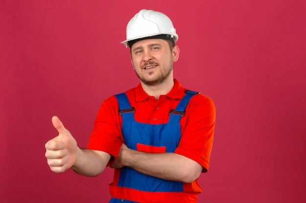 Baumeistermann, der bauuniform und sicherheitshelm trägt, der freundlich lächelnd zeigt daumen oben über isolierter rosa wand steht