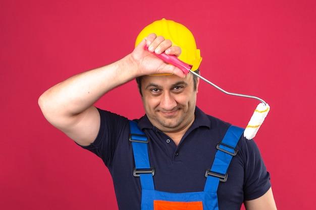 Baumeistermann, der bauuniform und sicherheitshelm trägt, der mit farbroller steht, der glücklich schaut und über isolierte rosa wand lächelt