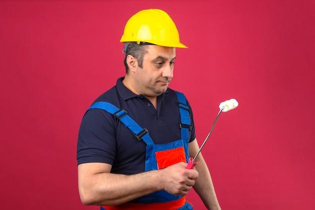 Baumeistermann, der bauuniform und sicherheitshelm trägt, der mit farbroller steht und es mit ernstem gesicht über isolierter rosa wand betrachtet