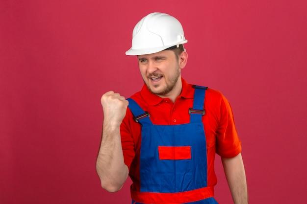Baumeistermann, der bauuniform und sicherheitshelm trägt, der mit glücklichem gesicht hebt, das faust nach einem siegesgewinnerkonzept erhöht, das über isolierter rosa wand steht