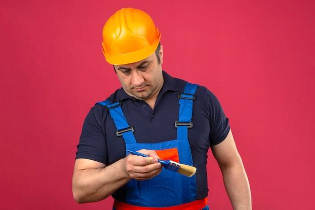 Baumeistermann, der bauuniform und sicherheitshelm trägt, der mit pinsel steht und es mit ernstem gesicht über isolierter rosa wand betrachtet