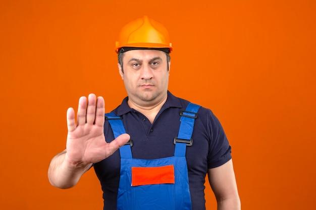 Baumeistermann, der bauuniform und sicherheitshelm trägt, der seine hand hält und stoppgeste über isolierte orange wand macht