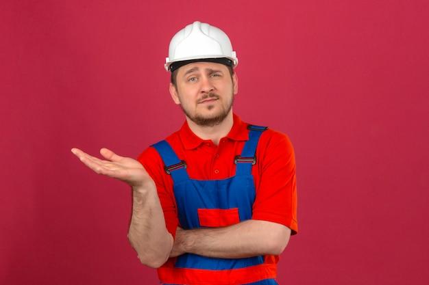 Baumeistermann, der bauuniform und sicherheitshelm trägt, der zur kamera lächelt, während sie mit hand präsentiert, die über isolierter rosa wand steht