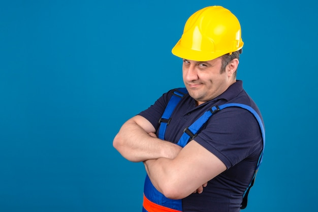 Baumeistermann, der bauuniform und sicherheitshelm trägt, die mit verschränkten armen stehen und skeptisch über isolierte blaue wand fühlen