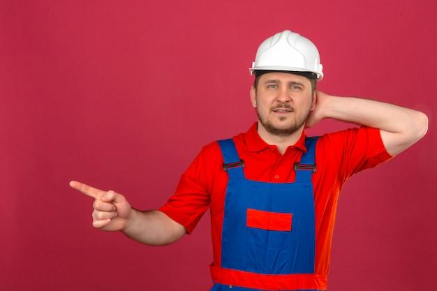 Baumeistermann, der bauuniform und sicherheitshelm trägt, zeigt finger zur seite und fühlt sich zweifelhaft stehend über isolierter rosa wand