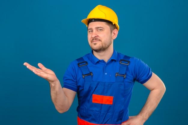 Baumeistermann, der bauuniform und sicherheitshelm trägt, zeigt mit offener handfläche, die kopienraum zeigt, der zuversichtlich über isolierte blaue wand lächelt