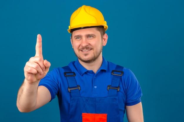 Baumeistermann, der bauuniform und sicherheitshelm trägt, zeigt nummer eins mit finger, der beiseite lächelnd freundlich steht über isolierter blauer wand steht